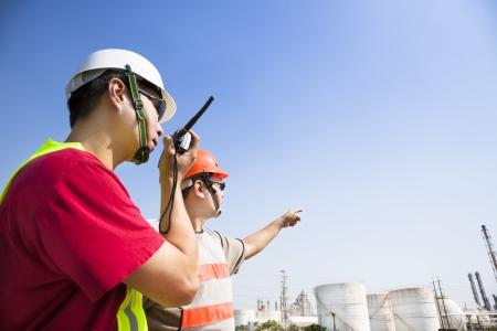 refinería de petróleo: dos trabajadores de las refinerías que buscan el fondo refinería grande