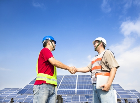 solar collector:  two engineers handshaking  before large solar power station