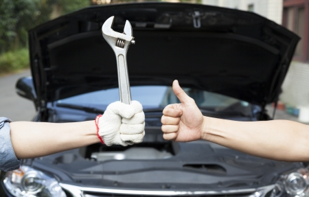 hand of mechanic with thumbs up and tool photo