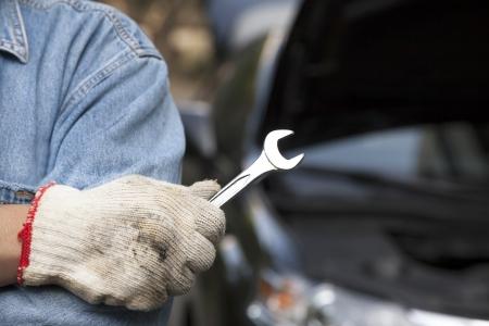 car repair shop: car technician holding the wrench