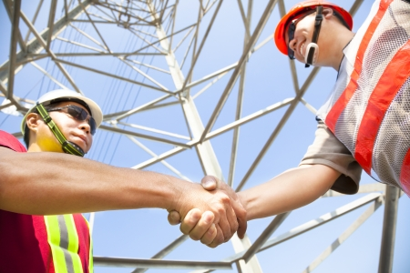 two power line tower workers with handshaking photo