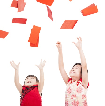 chinese dress: happy chinese new year.two asian kids trying to catch red envelope for good luck and rich