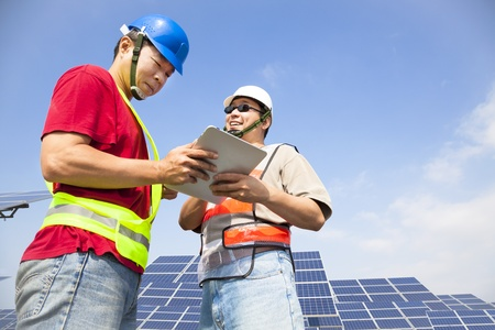 two workers  discussing with tablet pc before  solar power station photo