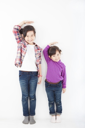 tall woman: two beautiful asian little girls standing together