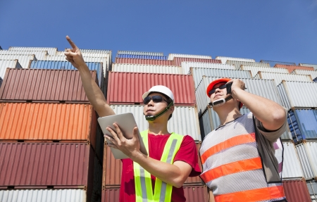 SHIPPING CONTAINERS: two workers with tablet pc and standing before stack of containers  Stock Photo