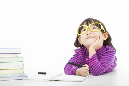 asiatique: petite fille pense ou rêve au cours de la préparation de devoirs Banque d'images