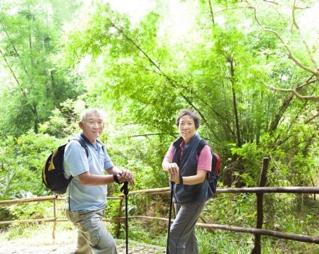 senioren wandelen: senior paar wandelen in de natuur met bamboe achtergrond