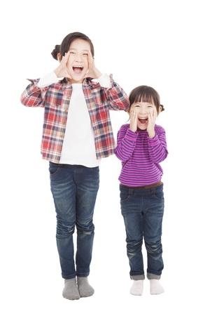shout: two beautiful asian little girls shouting together