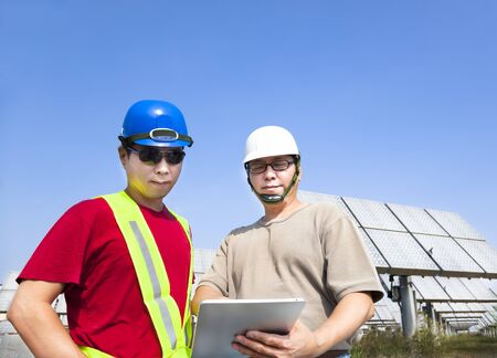 two contractors holding tablet pc and standing before solar panel tracking system photo