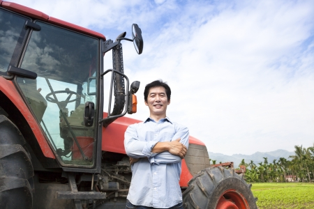 happy middle aged asian farmer with old tractor photo
