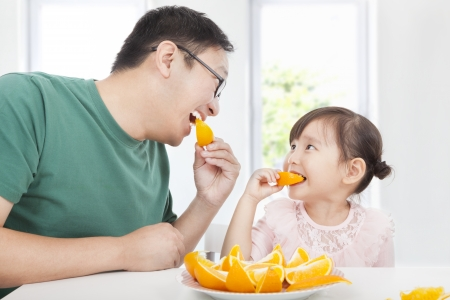 family dinner: happy little girl with father eating orange