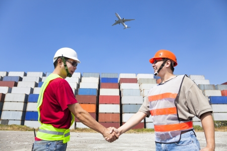 import and export business: two happy workers handshaking before transportation containers