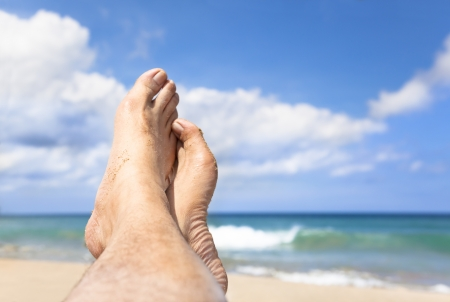 feet in sand: relaxed foot lying on the beach