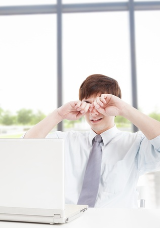 tired eyes: Young businessman with tired eyes and working in office Stock Photo