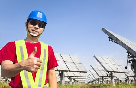 happy worker with thumb up and standing before solar panel tracking system photo