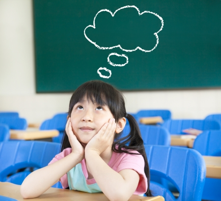 little girl in the classroom with thinking cloud symbol photo