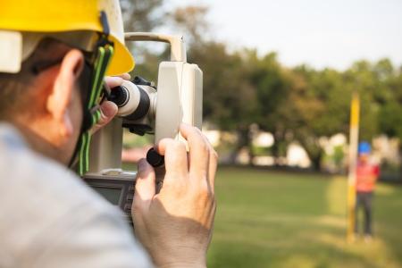 topografo: Ingeniero topógrafo con la pareja toma medidas en el campo Foto de archivo