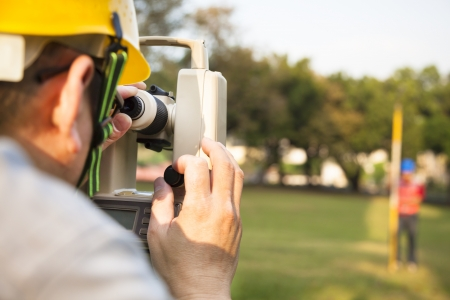 land: Surveyor engineer with partner making measure on the field