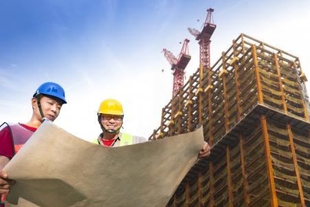 cantieri edili: due operai edili con gru giganti e costruzione