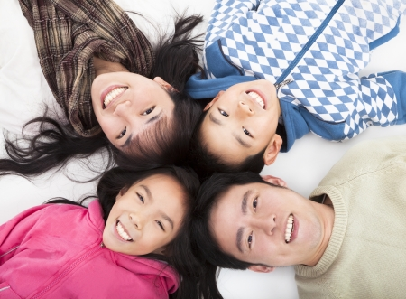 lying on the floor: Happy asian  family with heads together
