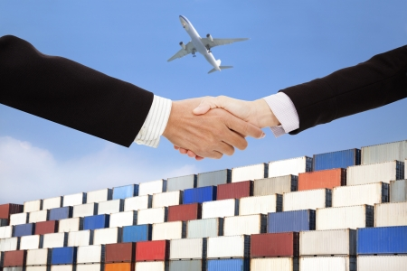 handshaking: international business trade and transportation concept.businessman and businesswoman handshaking with containers background
