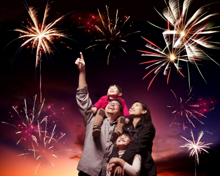night fireworks: happy family looking fireworks in the evening sky