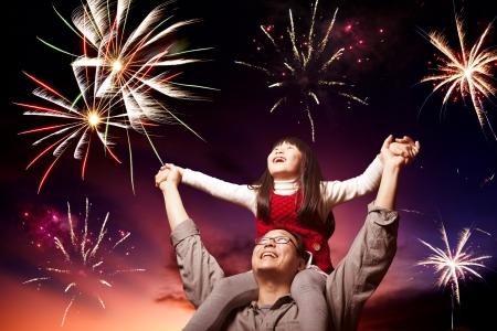 저녁 하늘에있는 아버지와 딸이보고 불꽃 놀이