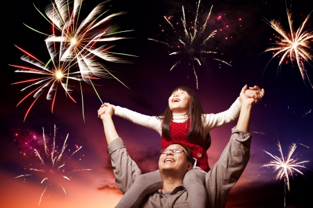 children celebration: father and daughter looking fireworks in the evening sky Stock Photo