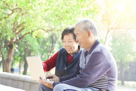 asian elderly: happy Senior couple surfing on internet with laptop Stock Photo