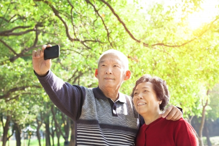 asian trees: Senior couple taking picture of themselves outdoor Stock Photo