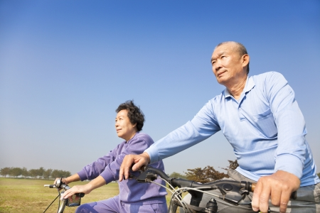 Happy elderly seniors couple biking  photo