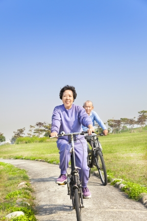 asian seniors couple biking in the park photo