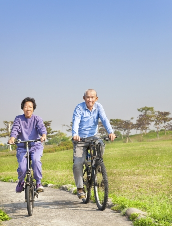 Happy asian seniors couple biking in the park photo