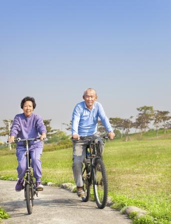 Happy asian seniors couple biking in the park Stock Photo - 17416437