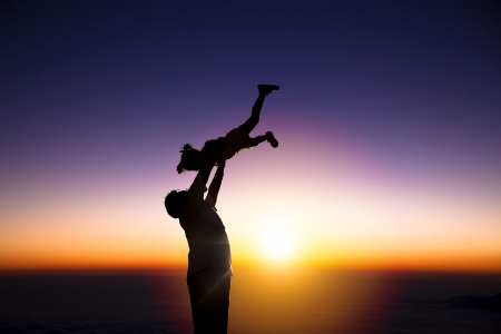 The silhouette of happy father and little girl with sunrise background Stock Photo - 17453169