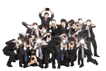 muchos fotógrafos que sostienen cámara apuntando a usted y aislados en blanco