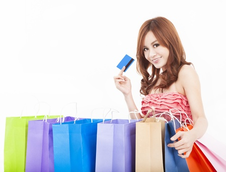 beautiful young woman holding credit card with shopping bags photo