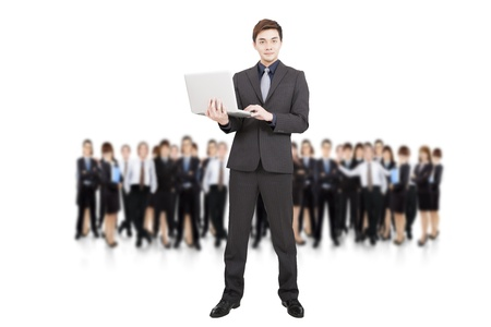 smart businessman holding laptop and successful business team photo