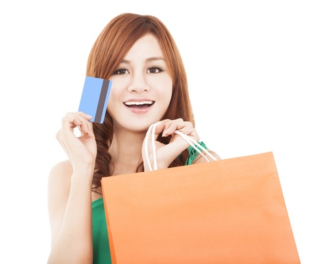 smiling young woman holding credit card with shopping bag photo