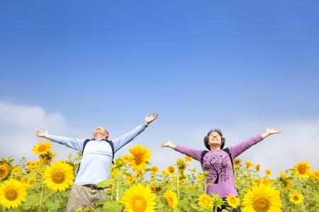 jubilados: posición relajada pareja de ancianos en el jardín de girasol Foto de archivo