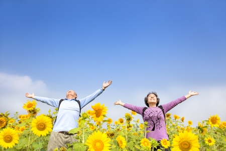 relaxed senior couple standing in the sunflower garden photo