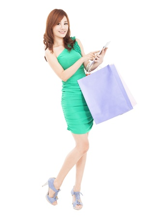 internet shopping: beautiful young woman with tablet pc and shopping bag