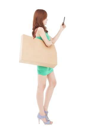 beautiful young woman with smart phone and shopping bag photo