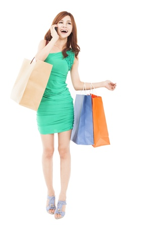 full length of Happy beautiful woman with shopping bags talking on the mobile phone photo