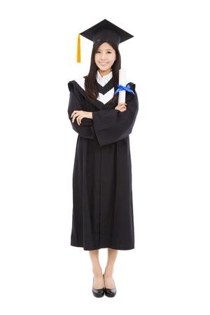 fondo de graduacion: de larga duraci�n y bella mujer joven de pie con la graduaci�n aislado sobre fondo blanco Foto de archivo
