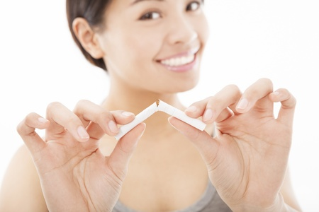 smiling woman breaking cigarette and no smoking concept photo