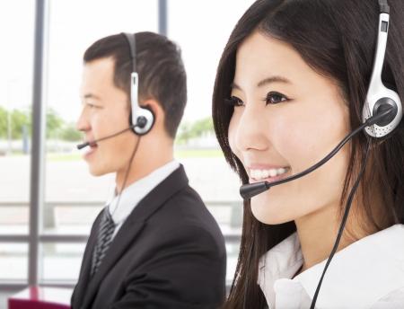 call center agent: sorridente uomo d'affari asiatico con l'agente di call center Archivio Fotografico