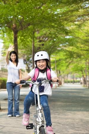 ir al colegio: ni�a feliz andar en bicicleta a la escuela Foto de archivo