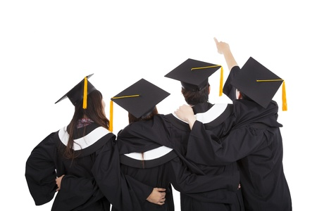 birrete de graduacion: cuatro estudiantes de posgrado apuntando y mirando hacia arriba Foto de archivo