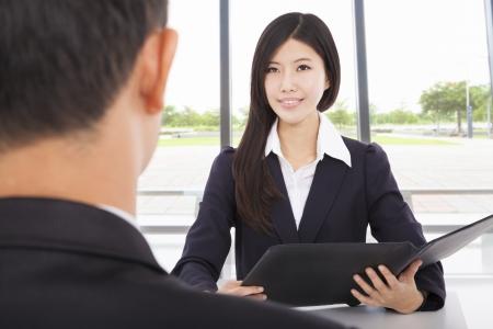 personas escuchando: mujer de negocios sonriente entrevista con el empresario en la oficina